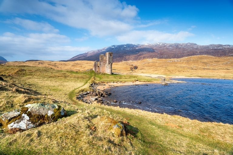 partially destroyed castle on loch edge