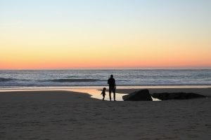 sunset on beach with 2 silhouettes of kid and father