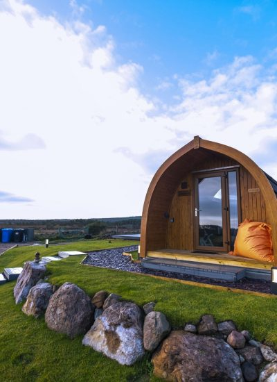 Front view of glamping pod with orange beanbag by door book brora