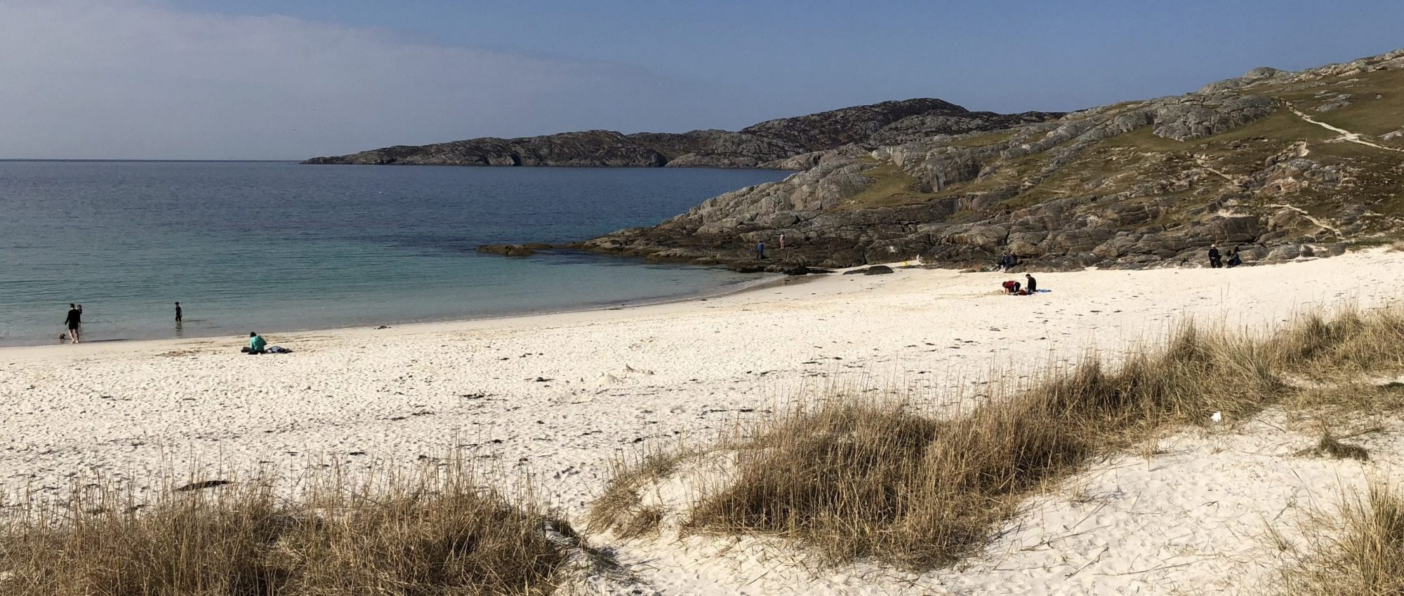 White sandy beach in bay with rocky coves