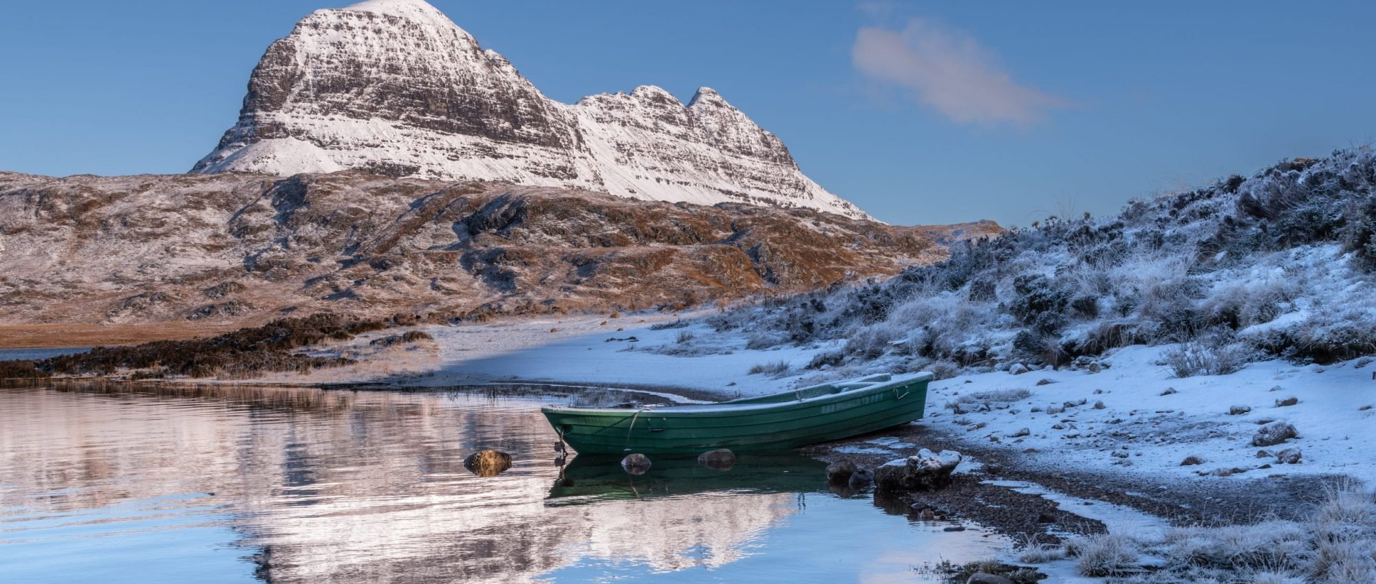 small green boat on snowy day with Suilven hill in background